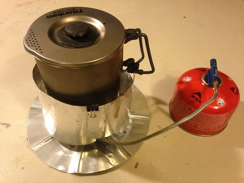 The Olicamp Xcelerator Titanium stove with a windscreen.
